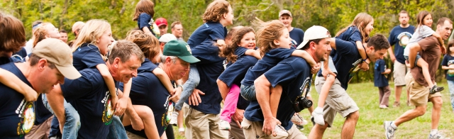 Dads and daughters at the start of a piggy back race in the Y Guides and Princesses program