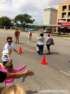 Pamela's family high fives her son as he heads for the finish line.